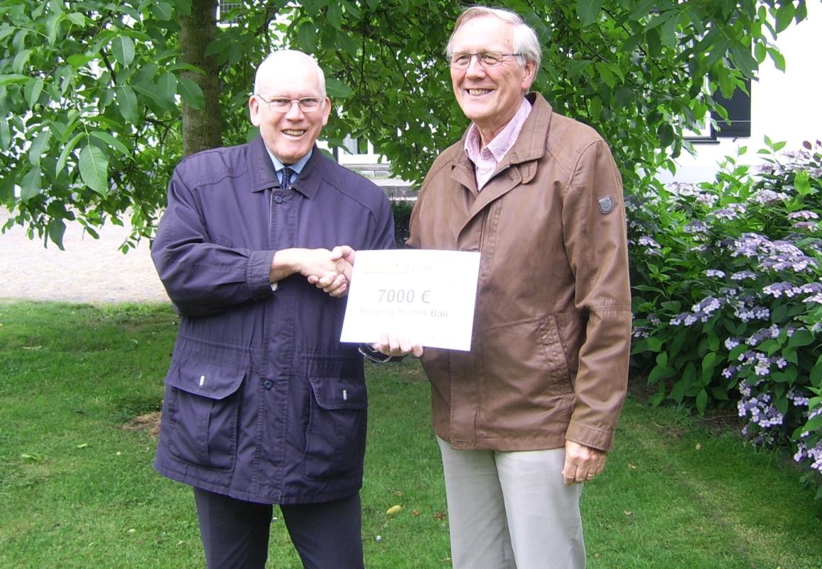 Pastoor Spijkers overhandigt de cheque aan Jan Jansen